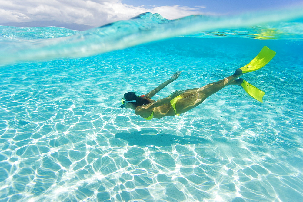 Woman snorkeling in tropical ocean water, Over/under view. - 1116-27990