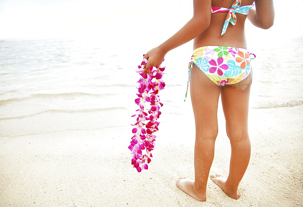 Hawaii, Oahu, Young girl holding an orchid lei, view from behind.