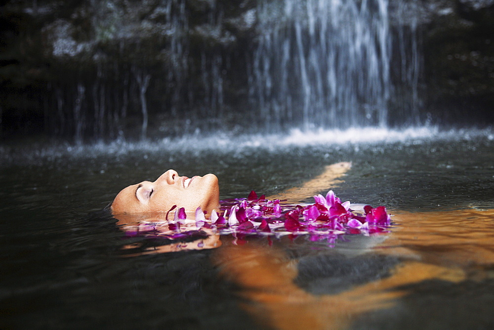 Hawaii, Oahu, Manoa Falls, Beautiful female with orchids leis floating at the bottom of Manoa Waterfalls. - 1116-28168