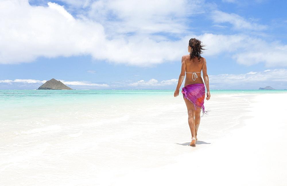 Hawaii, Oahu, Lanikai Beach, Woman walking along sandy shore.
