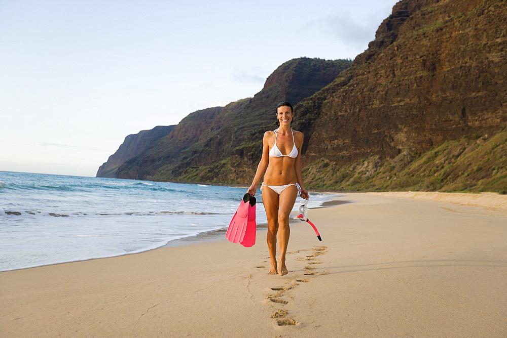 Hawaii, Kauai, Polihale Beach, Woman walking along sandy shore with snorkel gear, Evening glow.