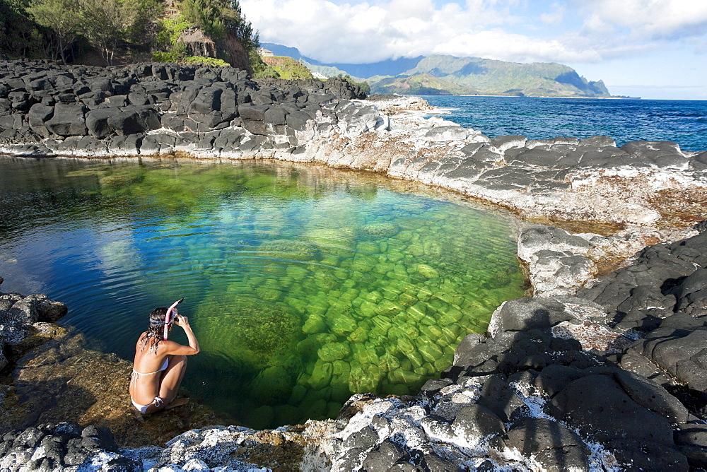 Hawaii, Kauai, Princeville, Queens Bath, Woman sitting on water's edge wearing snorkel gear.