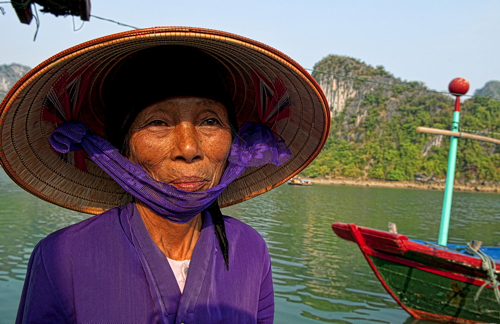 South East Asia, Vietnam, Ha Long Bay, Portrait of a  Vietnamese woman, Harbor in background.