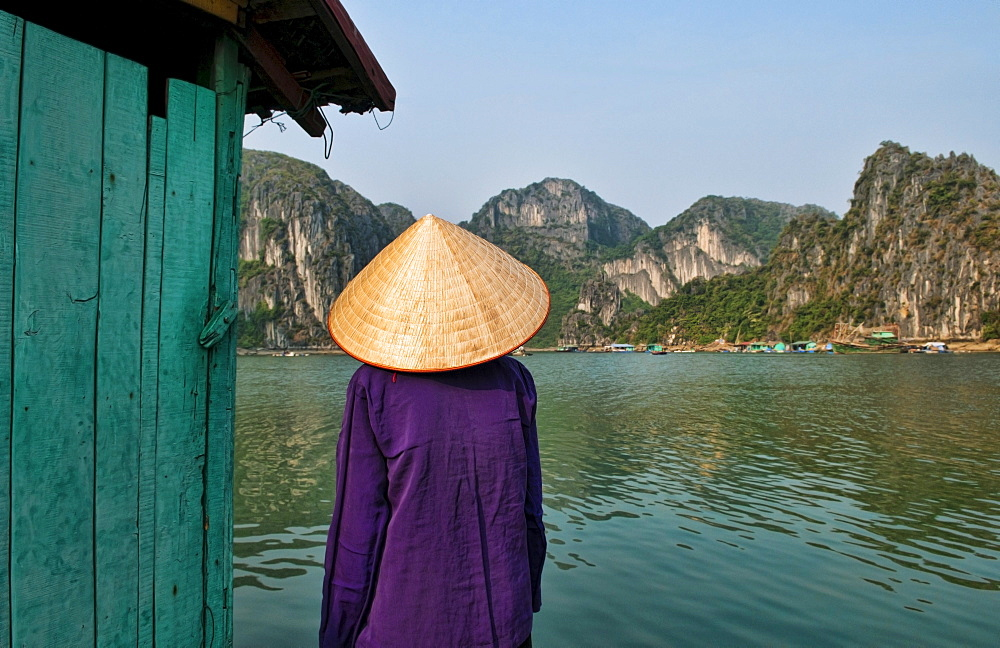 South East Asia, Vietnam, Ha Long Bay, Portrait of a  Vietnamese woman from behind, Harbor in background.