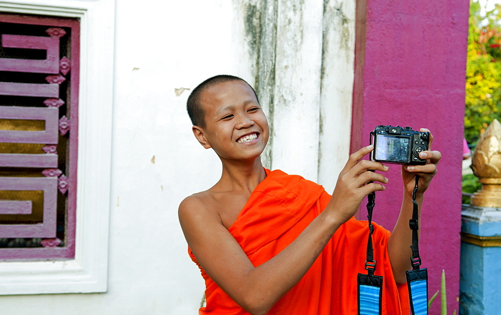 South East Asia, Laos, Luang Prabang, A young monk laughs as he takes his own picture with a visitor's camera.