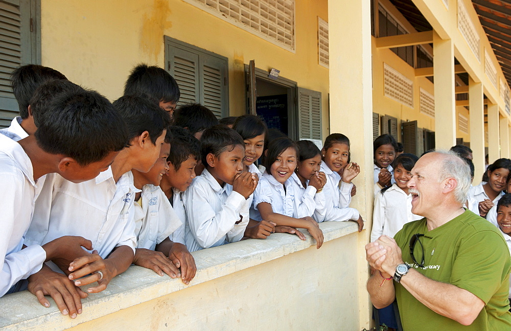 South East Asia, Cambodia, Siem Reap, A group of young school children laugh while tourist teaches them to make noises with their hands.