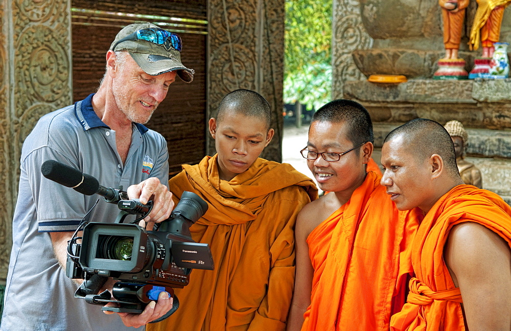 South East Asia, Cambodia, Siem Reap, Bhuddest Temple, Videographer shows video footage to three young monks.