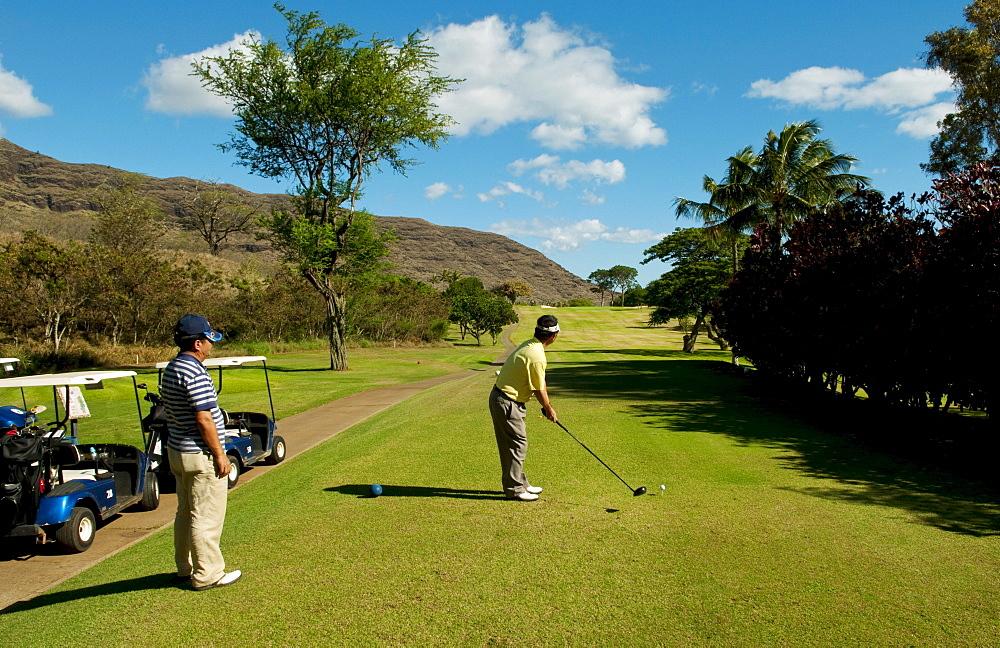 Hawaii, Oahu, Waianae, Makaha Resort, Two Japanese men play the 15th hole.