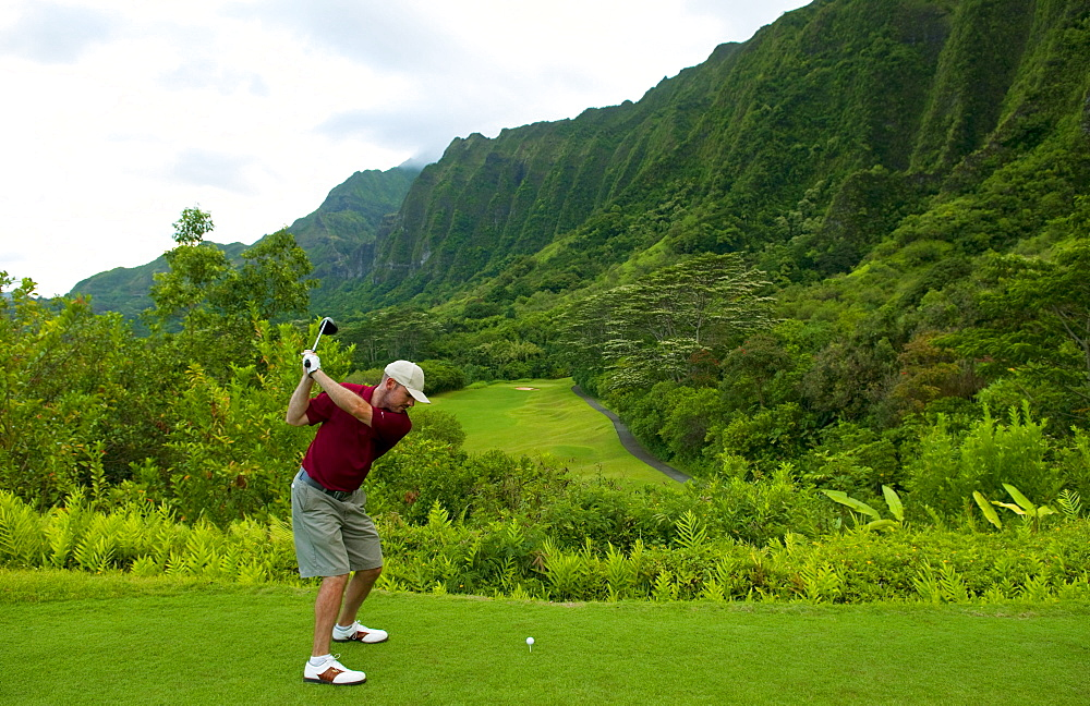 Hawaii, Oahu, Honolulu, Ko'olau Golf Course, Man driving on the 15th hole with beautiful mountain view.