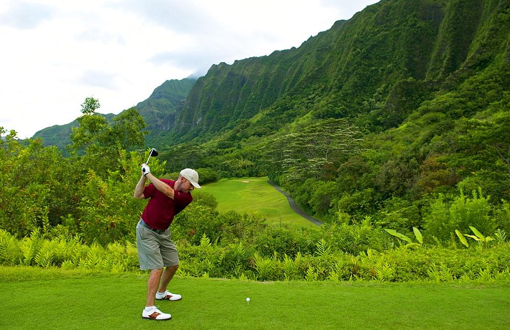 Hawaii, Oahu, Honolulu, Ko'olau Golf Course, Man driving on the 15th hole with beautiful mountain view.