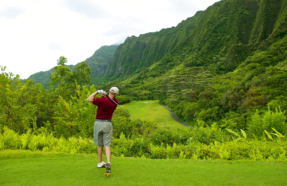Hawaii, Oahu, Honolulu, Ko'olau Golf Course, Man tees off at the fifteenth hole.