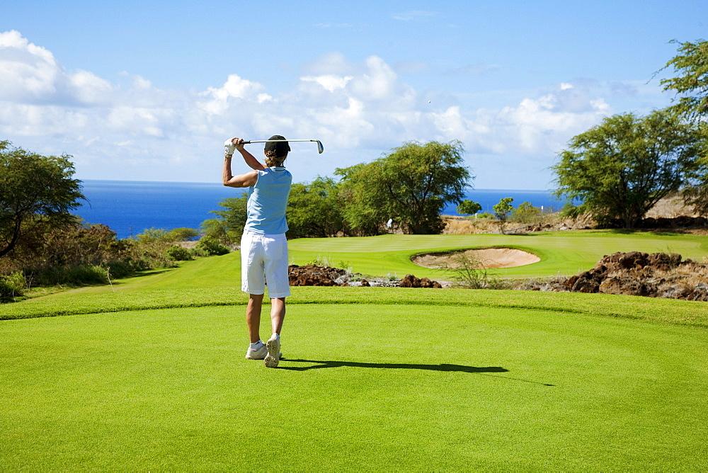 Hawaii, Lanai, Woman hitting a tee shot on The Challenge at Manele golf course.