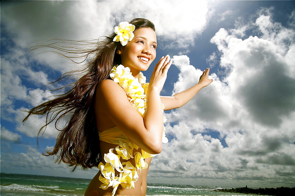 Hawaii, Kauai, Kealia, Beautiful Hawaiian girl dancing hula on ocean shoreline.