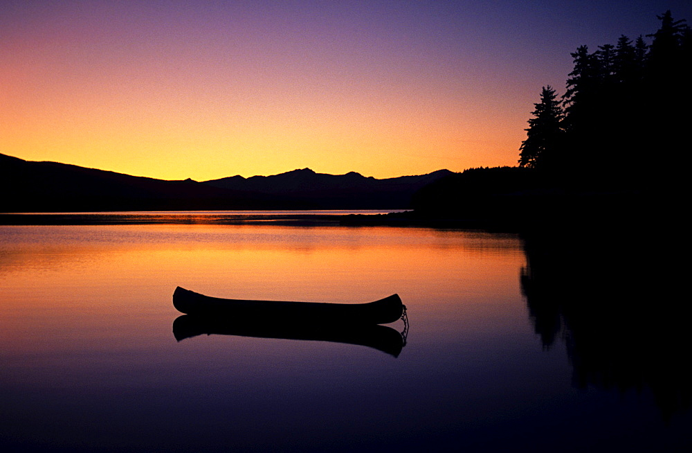 Alaska, Canoe floating on calm lake at sunset.