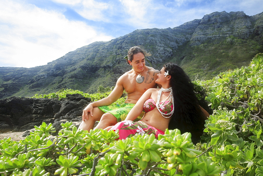 Hawaii, Oahu, Makapuu, Male and female hula dancers sit on the shore