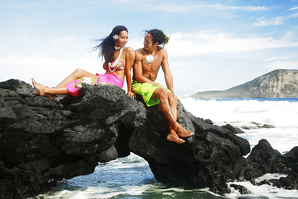Hawaii, Oahu, Makapuu, Male and female hula dancers sit on a rock posing.