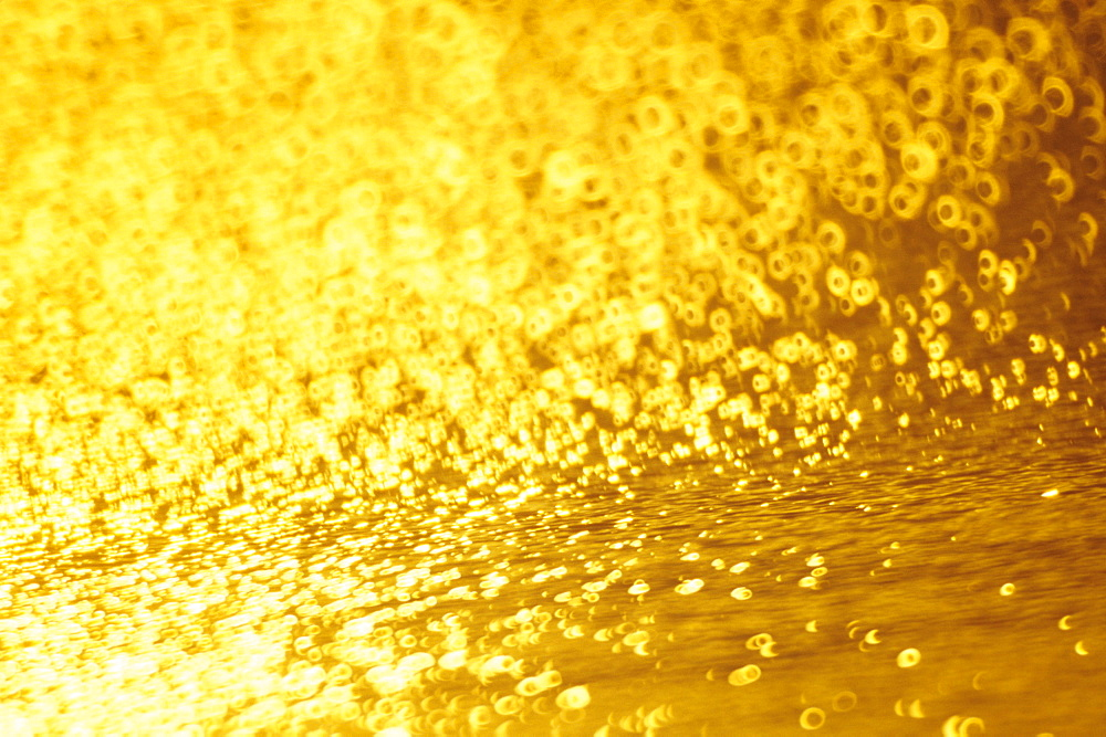 Closeup of golden shimmering reflections off water.