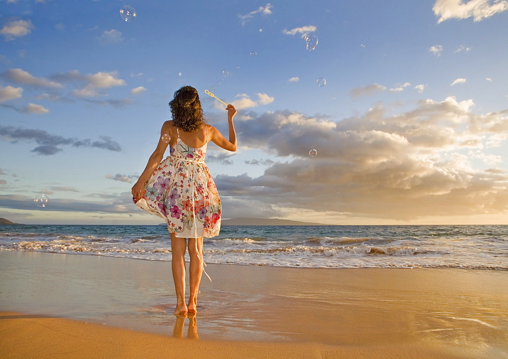 Hawaii, Maui, Woman standing on the shore of remote tropical location blowing bubbles.