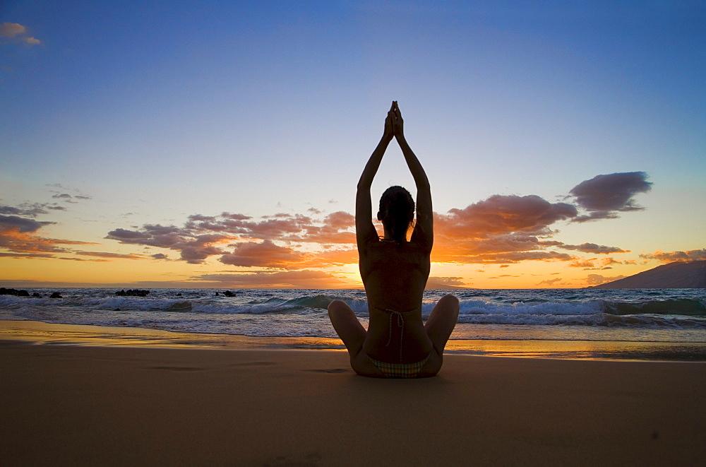 Hawaii, Maui, Silhouette of beautiful girl doing yoga on the beach.