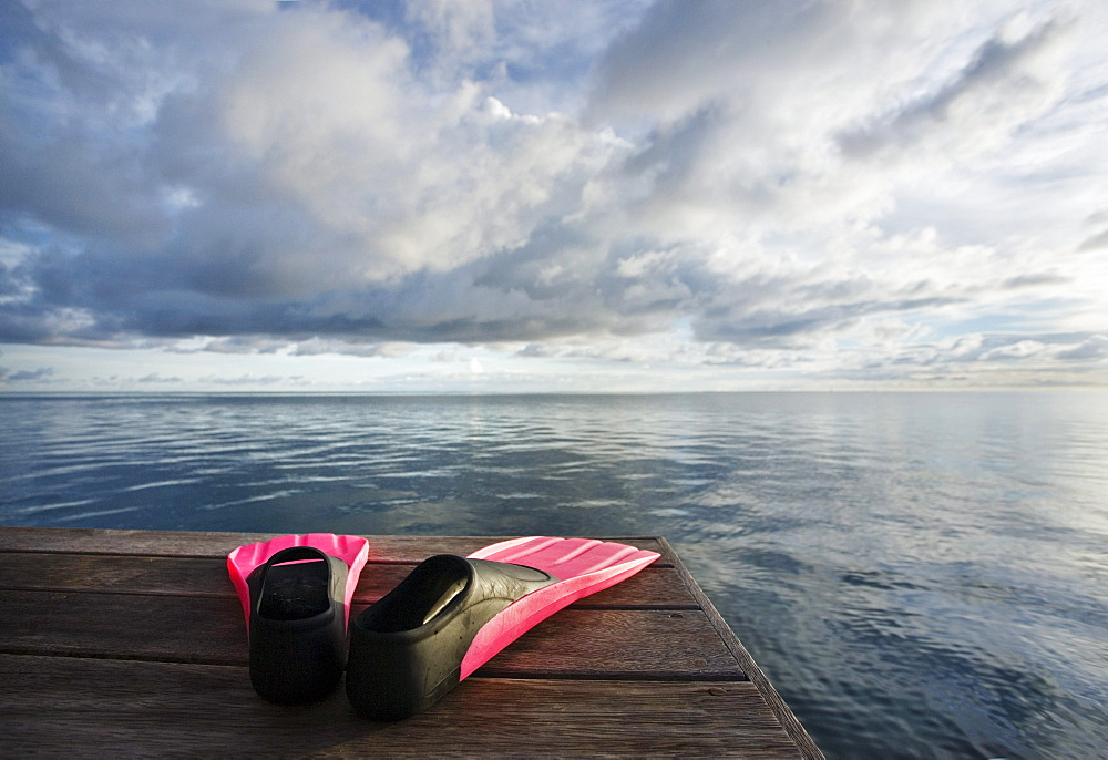 Hawaii, Pink fins on dock at sunset.