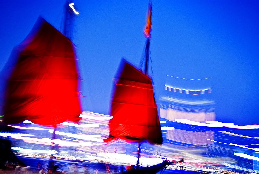 Hong Kong, Tsim Sha Tsui K, A red sailed chinese junk boat passes in front of Hong Kong Island.