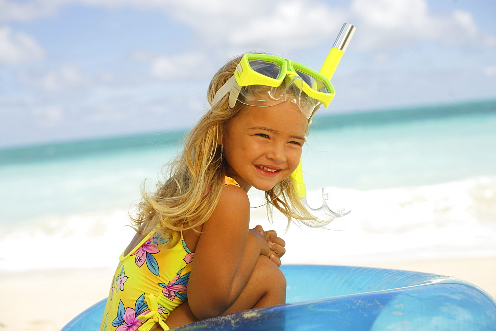 Hawaii, Oahu, little girl poses on beach with snorkel.
