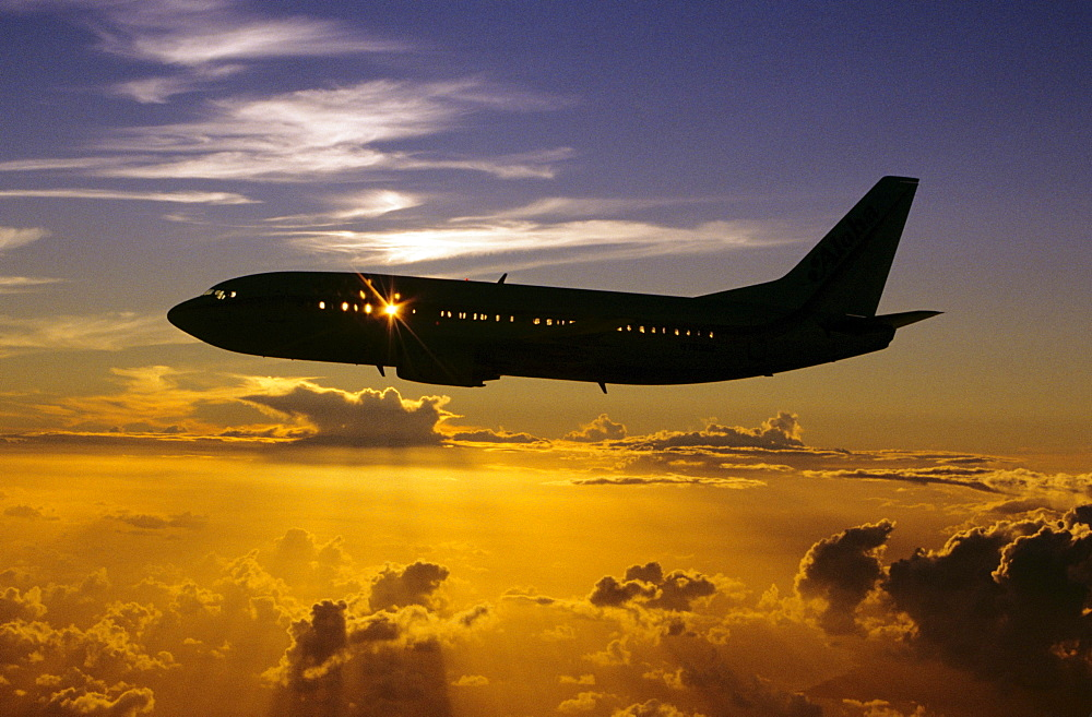 Hawaii, Airplane in silhouette sunset in sky.