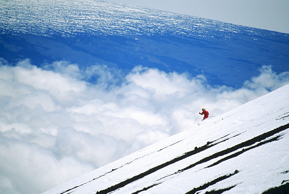 Hawaii, Big Island, Mauna Kea, Woman skiing downhill at high elevation.