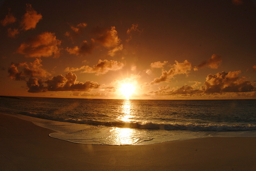 Hawaii, Oahu, North Shore, bright sun reflecting on ocean as it sinks low in the sky, golden light.