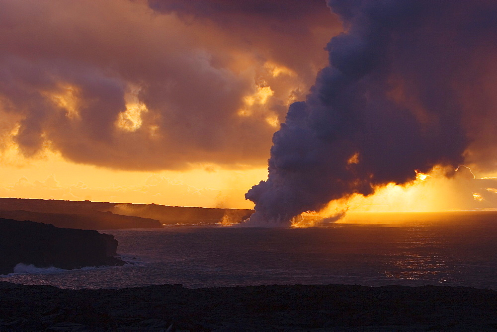 Hawaii, Big Island, Kalapana, Steam cloud from lava entering Pacific Ocean from Kilauea at sunset.