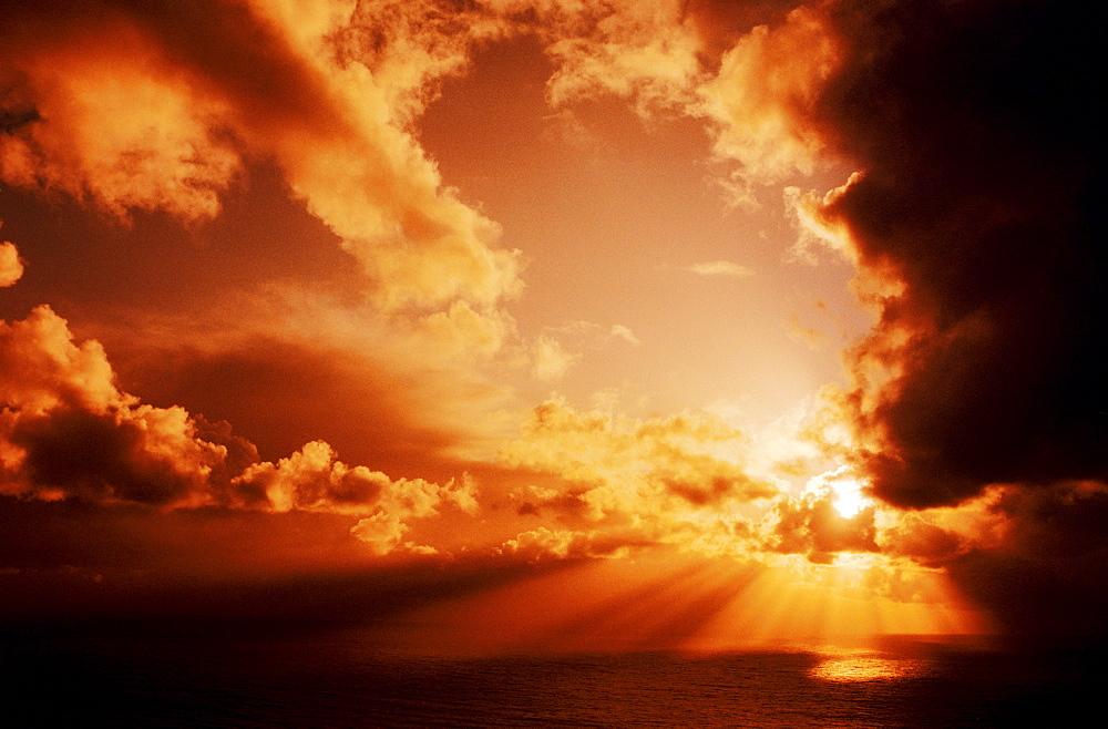Orange sunset over ocean, Sunrays bursting through puffy clouds.