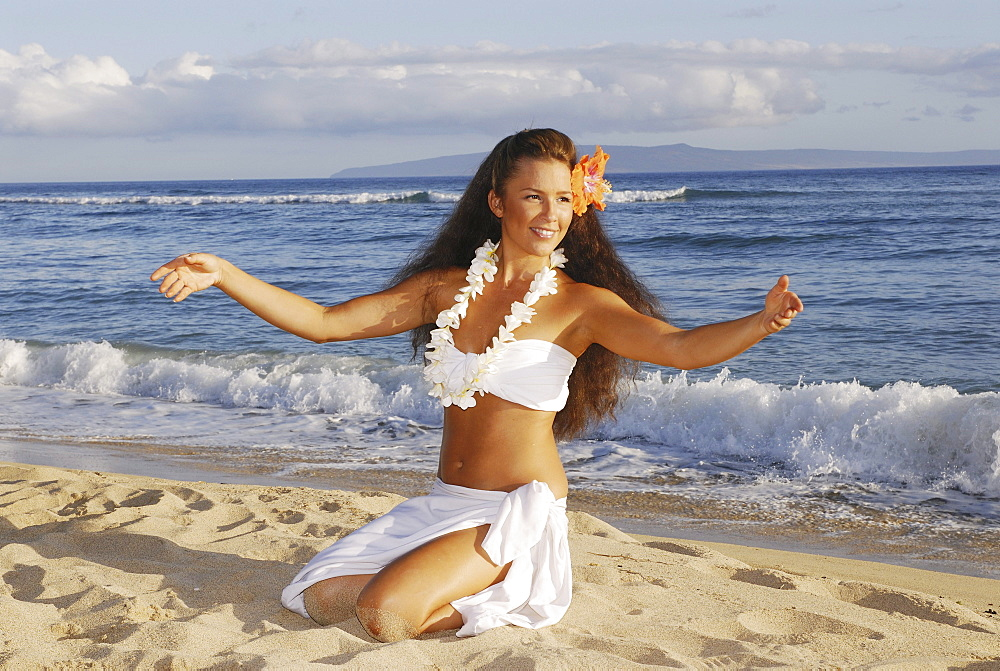 Beautiful Hawaiian girl dancing hula on ocean shoreline.