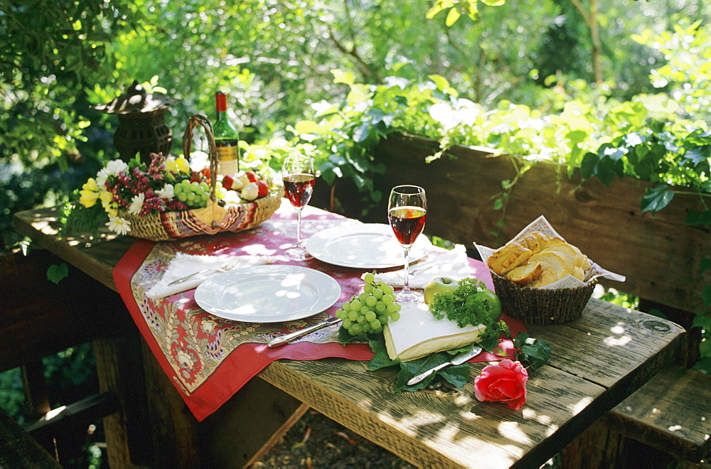 Alfresco lunch on wooden table in outdoor setting.