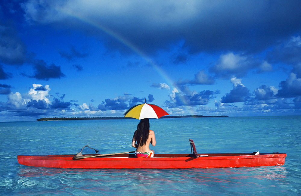 French Polynesia, Tetiaroa, Woman with umbrella in outrigger canoe floating on clear turquoise ocean, View from behind.