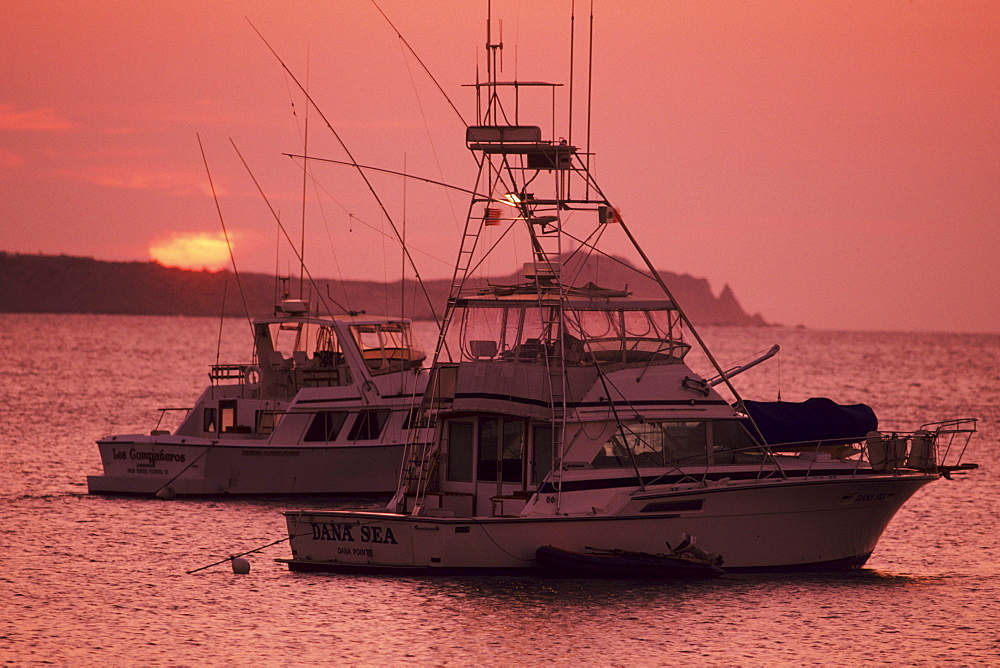 Mexico, Cabo San Lucas, Fishing boats floating on ocean at sunset.