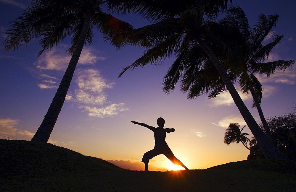 Hawaii, Maui, Olowalu, woman doing yoga at sunset under palm trees.