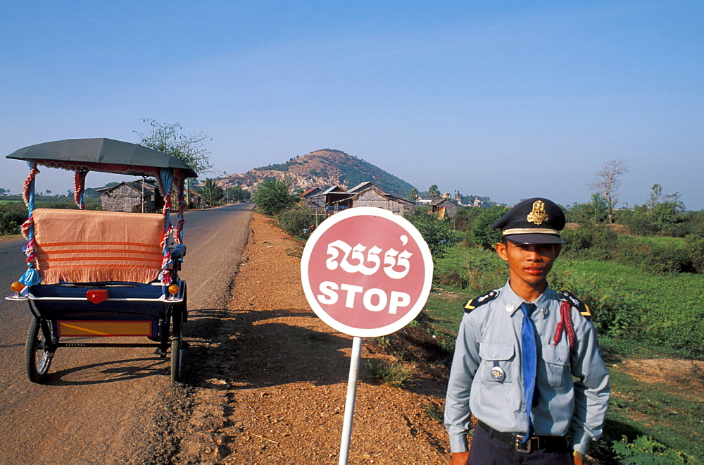Cambodia, Lake Tonle Sap Village, Policeman standing beside road with stop sign.