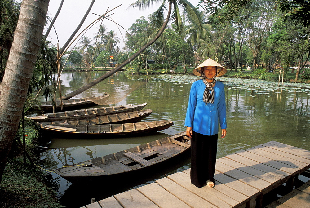 Vietnam, Mekong Delta, Woman in traditional clothing, standing on dock near river and old boats.