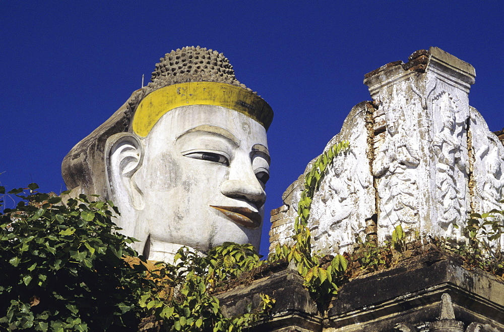 Burma (Myanmar), Mandalay, Close-up of Colossal, head of Buddha against blue sky.