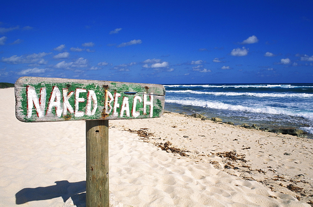 Mexico, Yucatan Peninsula, Cozumel, Naked Beach sign in sand, ocean and blue sky in background.