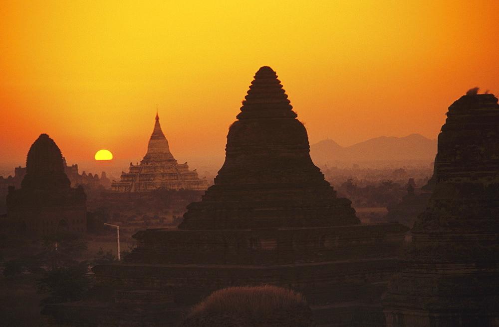 Burma (Myanmar), Bagan, Shwesandaw Paya, temples silhouetted against orange sunset.