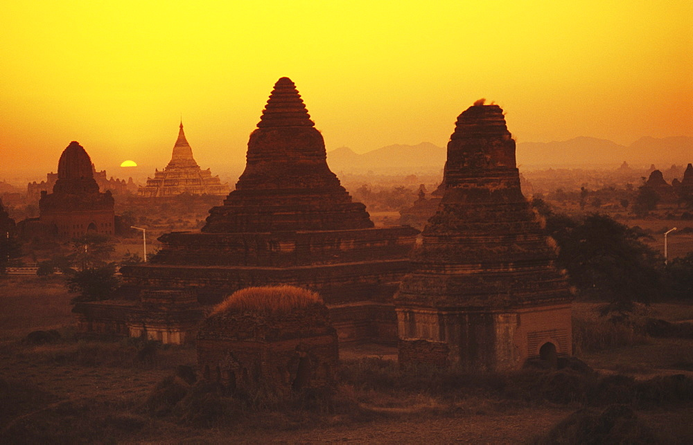 Burma (Myanmar), Bagan, Shwesandaw Paya, overview of temples against orange sky and setting sun.