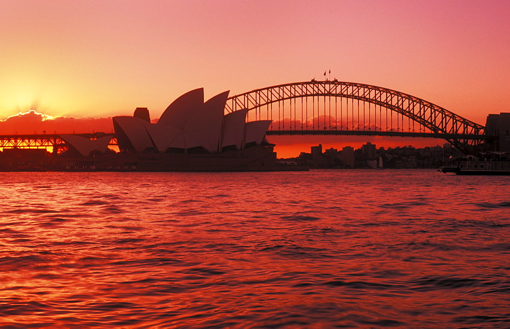 Australia, New South Wales, Sydney, Opera House and Harbour Bridge, bright red and pink sunset.