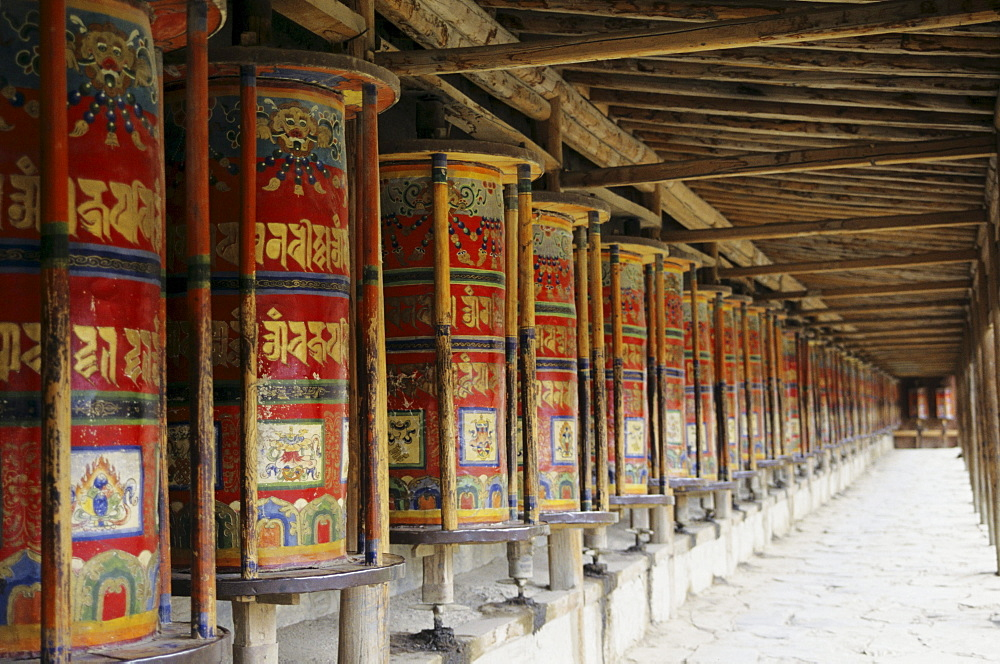 China, Xiahe, Labrange Monastary, row of colorful prayer wheels