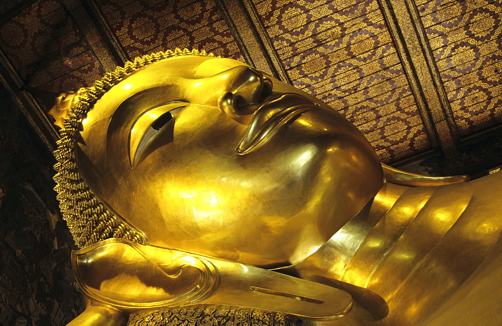 Thailand, Bangkok, Wat Po Close-up of gold Reclining Buddha head