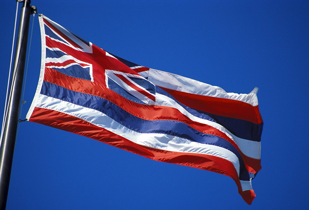 Hawaii, Hawaiian Flag blowing in the wind against deep blue sky
