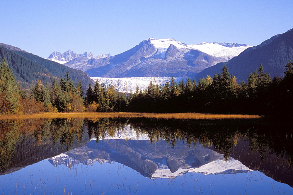 Alaska, Juneau, Mendenhall Glacier, Tongass National Forest, Mountains reflect in a mountain lake.