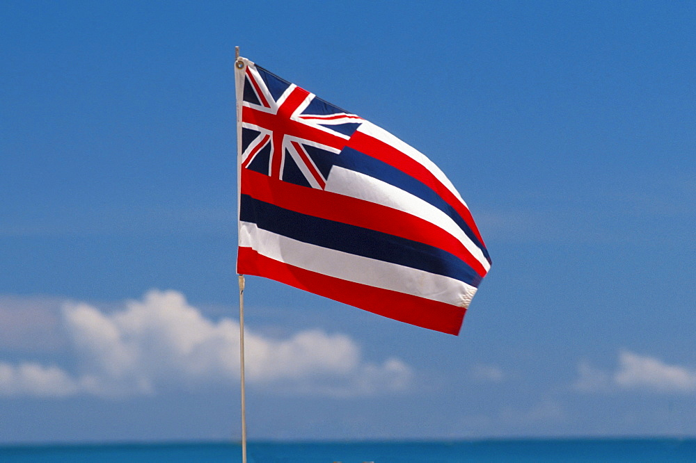 Hawaii, Hawaiian Flag, blue sky and clouds, ocean and horizon in foreground
