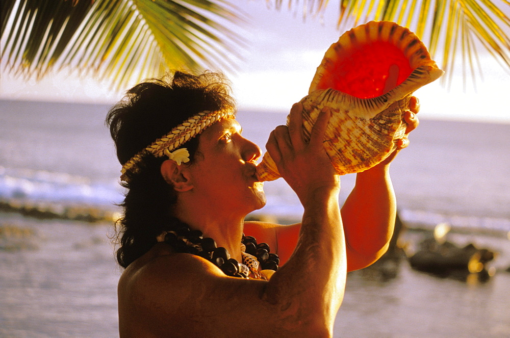Hawaii, Native local Man at ocean blowing conch shell with shell haku