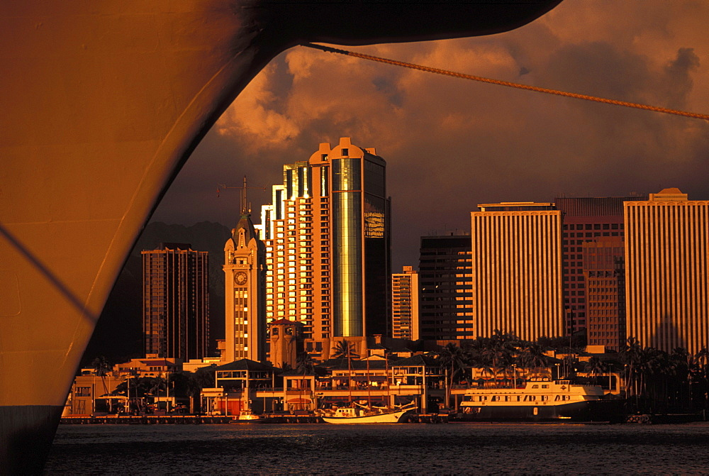 Hawaii, Oahu, Honolulu, Aloha Tower, Honolulu harbor, and downtown cast in a golden hue framed with ship